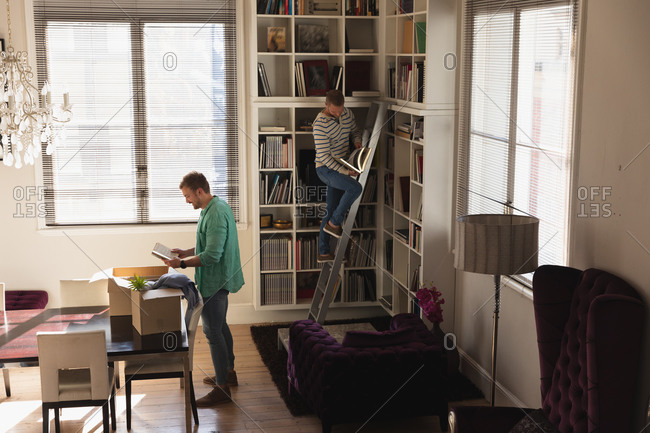 Side view of a Caucasian male couple moving in to a new apartment, unpacking their belongings from cardboard boxes and putting them on shelves, standing on a ladder.