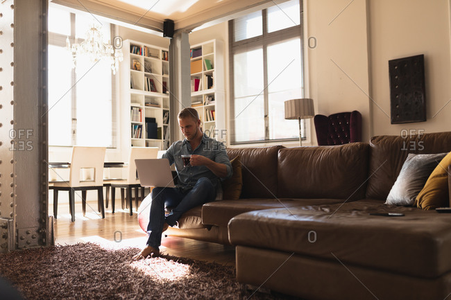Front view of a young Caucasian man spending time at home, sitting on the sofa, using his laptop computer and holding a cup of hot beverage.
