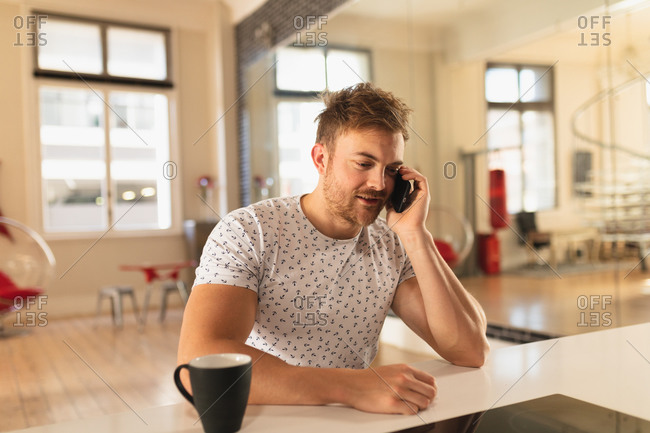Front view of a young Caucasian man spending time at home, sitting in the kitchen with a cup of beverage, talking on the smartphone.
