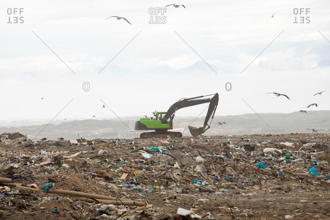 Flock of birds flying over digger working and clearing rubbish piled on a landfill full of trash with cloudy overcast sky in the background. Global environmental issue of waste disposal.