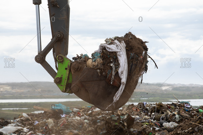 Close up of a digger working and clearing rubbish piled on a landfill full of trash with cloudy overcast sky in the background. Global environmental issue of waste disposal.