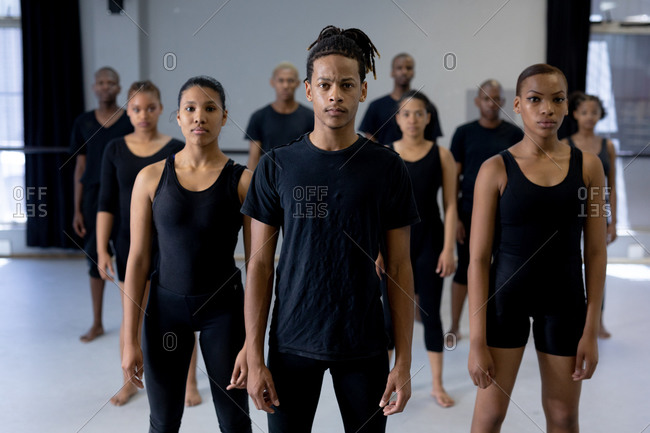 Front view of a mixed race modern male dancer wearing black clothes, standing in front of a multi-ethnic group of fit male and female dancers, looking straight into a camera.