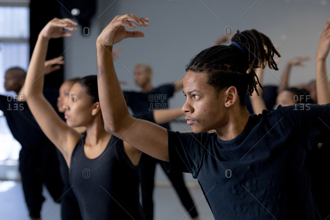 Side view close up of a multi-ethnic group of fit male and female modern dancers wearing black outfits practicing a dance routine during a dance class in a bright studio, holding their right arms up.
