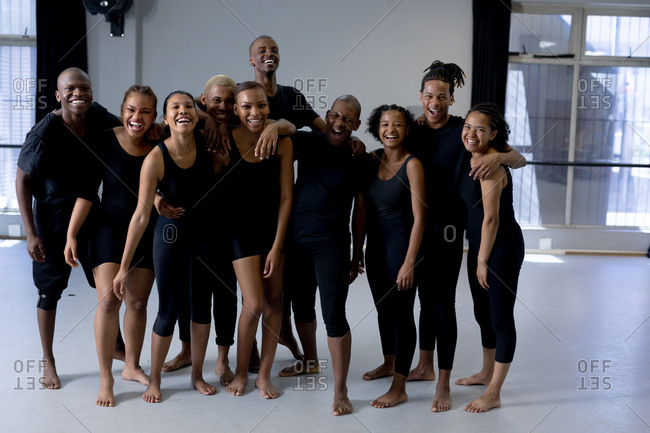 Front view of a multi-ethnic group of fit male and female modern dancers wearing black outfits practicing a dance routine during a dance class in a bright studio, standing together, smiling and looking straight into a camera.