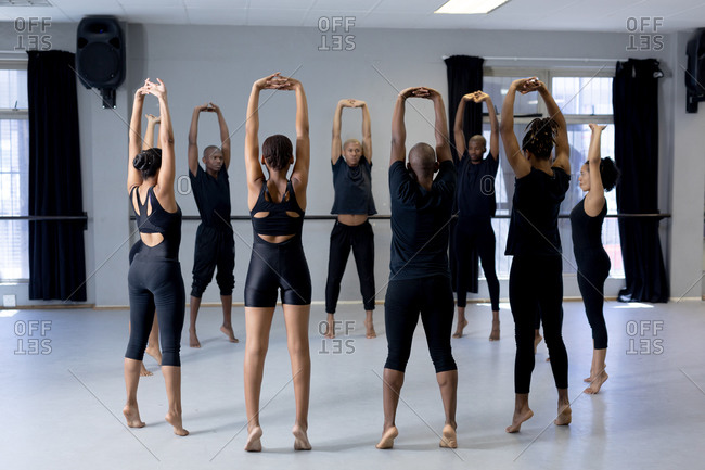 Rear view of a multi-ethnic group of fit male and female modern dancers wearing black outfits practicing a dance routine during a dance class in a bright studio, creating a circle and stretching up keeping hands above their heads.
