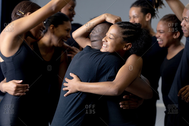 Side view close up of a multi-ethnic group of fit male and female modern dancers wearing black outfits practicing a dance routine during a dance class in a bright studio, embracing and smiling.
