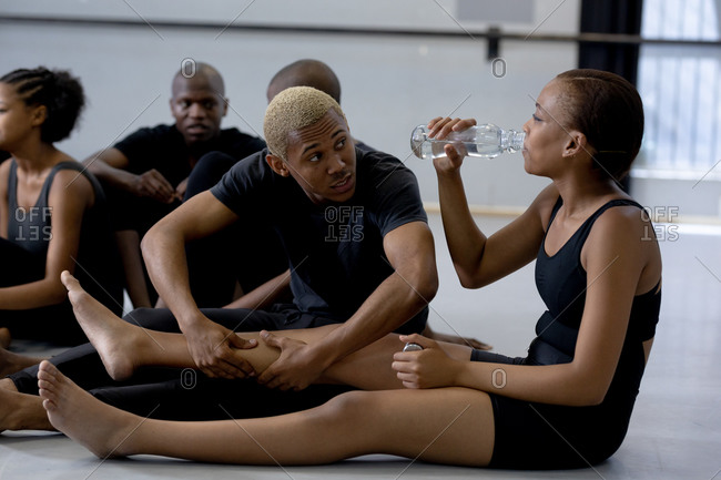 Side view close up of a multi-ethnic group of fit male and female modern dancers wearing black outfits practicing a dance routine during a dance class in a bright studio, enjoying a break, sitting on the floor, interacting and drinking water.