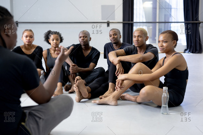 Rear view close up of a mixed race fit male modern dancer wearing black outfit, sitting on the floor and talking to a group of dancers during a dance class in a bright studio.