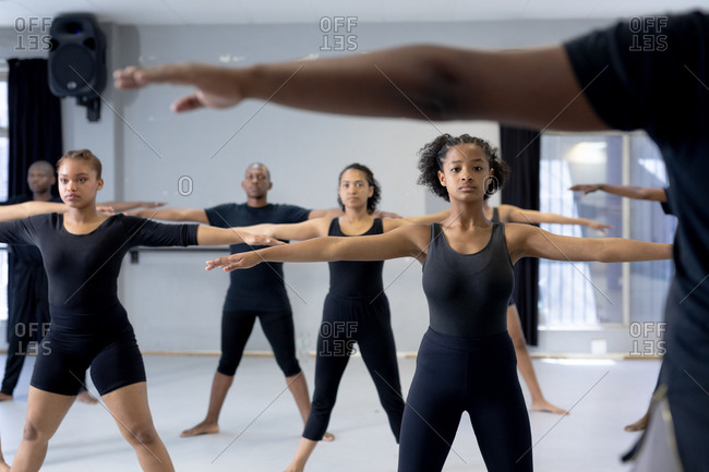 Front view of a multi-ethnic group of fit male and female modern dancers wearing black outfits practicing a dance routine during a dance class in a bright studio, spreading their arms.