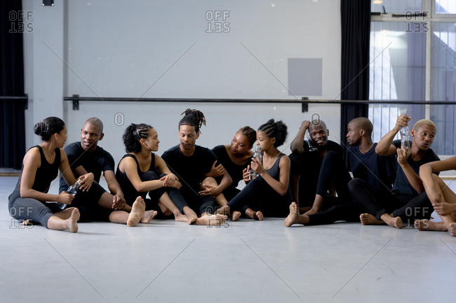 Side view of a multi-ethnic group of fit male and female modern dancers wearing black outfits practicing a dance routine during a dance class in a bright studio, enjoying a break, sitting on the floor, interacting and drinking water.