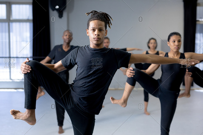 Front view of a mixed race modern male dancer wearing black clothes, standing in front of a multi-ethnic group of fit male and female dancers, holding his leg up and reaching out his arm.