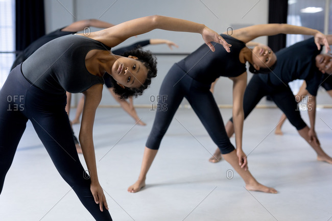Front view of a multi-ethnic group of fit male and female modern dancers wearing black outfits practicing a dance routine during a dance class in a bright studio, stretching up.