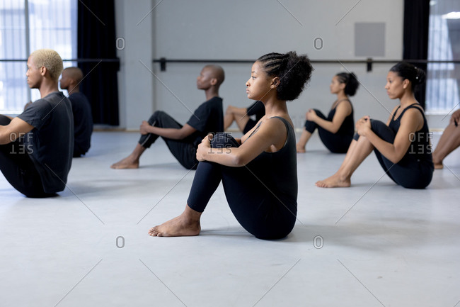 Side view of a multi-ethnic group of fit male and female modern dancers wearing black outfits practicing a dance routine during a dance class in a bright studio, sitting on the floor and stretching up.