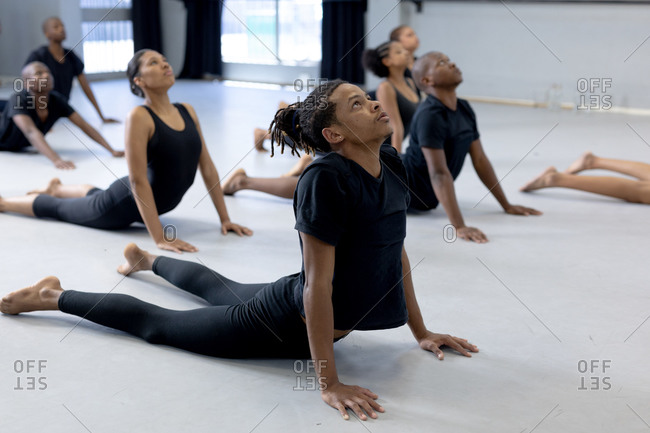 Side view of a multi-ethnic group of fit male and female modern dancers wearing black outfits practicing a dance routine during a dance class in a bright studio, lying on the floor and stretching up.