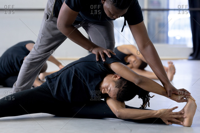 Side view of a two mixed race fit male modern dancers wearing black outfits practicing a dance routine during a dance class in a bright studio, supporting each other during stretching up, with other dancers exercising in the background.