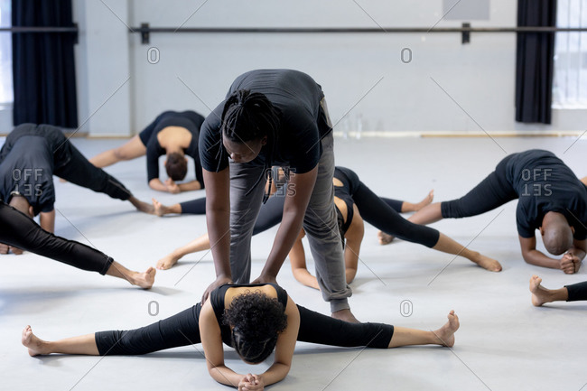 Front view of a mixed race fit male modern dancer wearing black outfit, supporting a female dancer while stretching up during a dance class in a bright studio, with other dancers exercising in the background.