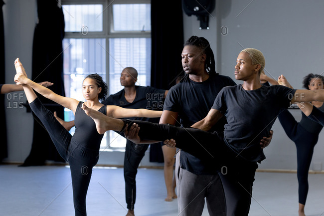 Front view of a mixed race fit male modern dancer wearing black outfit, supporting a male dancer while stretching up during a dance class in a bright studio, with other dancers exercising in the background.