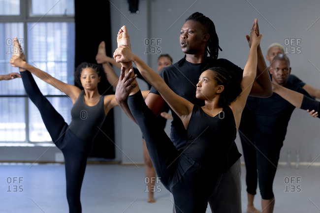 Mixed race fit male modern dancer dressed in black supporting a female dance while stretching during a dance class in a bright studio