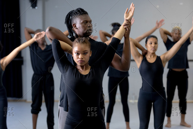 Fit male modern dancer dressed in black supporting a female dance while stretching during a dance class in a bright studio
