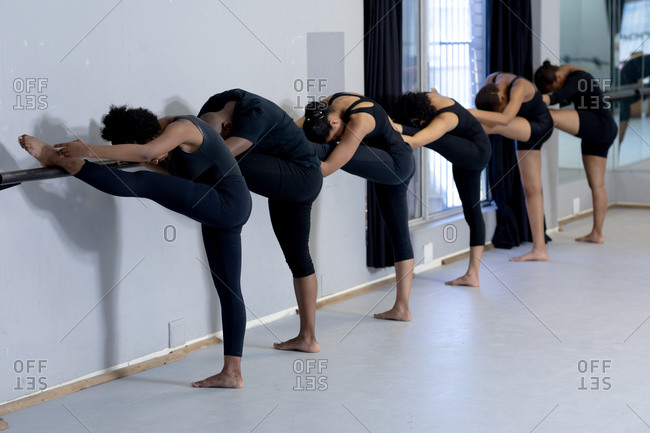 Side view of a multi-ethnic group of fit male and female modern dancers wearing black outfits practicing a dance routine during a dance class in a bright studio, standing by a handrail and stretching up.