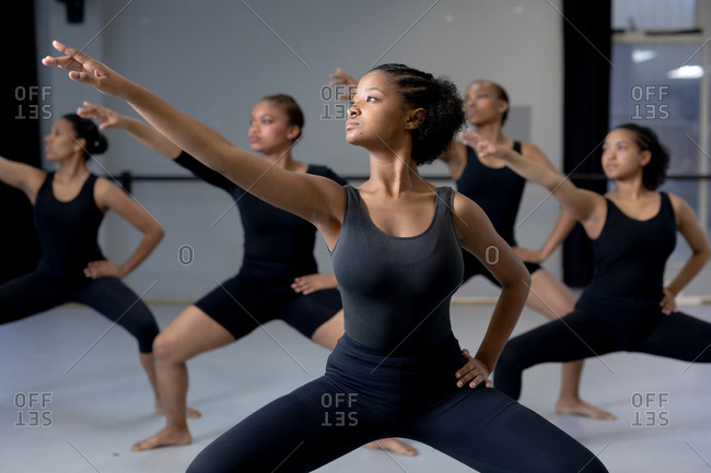Front view of a multi-ethnic group of fit female modern dancers wearing black outfits practicing a dance routine during a dance class in a bright studio, spreading their arms.