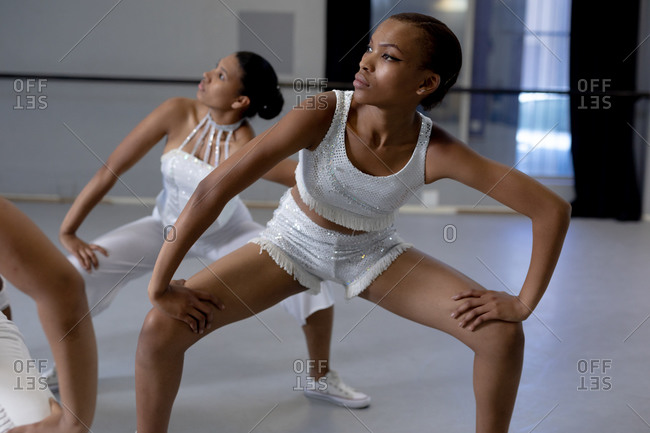 Front view close up of two mixed race fit female modern dancers wearing white outfits practicing a dance routine during a dance class in a bright studio.