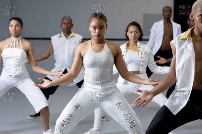Front view of a multi-ethnic group of fit male and female modern dancers wearing white outfits practicing a dance routine during a dance class in a bright studio.