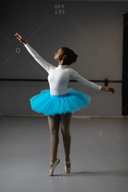 Front view of a mixed race female ballerina wearing white tricot and blue tutu, dancing in a bright studio, rising her arm.