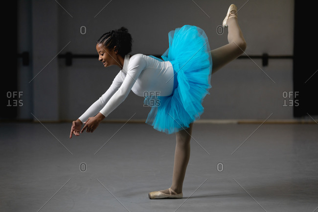 Side view of a mixed race female ballerina wearing white tricot and blue tutu, dancing in a bright studio, rising her leg and smiling.