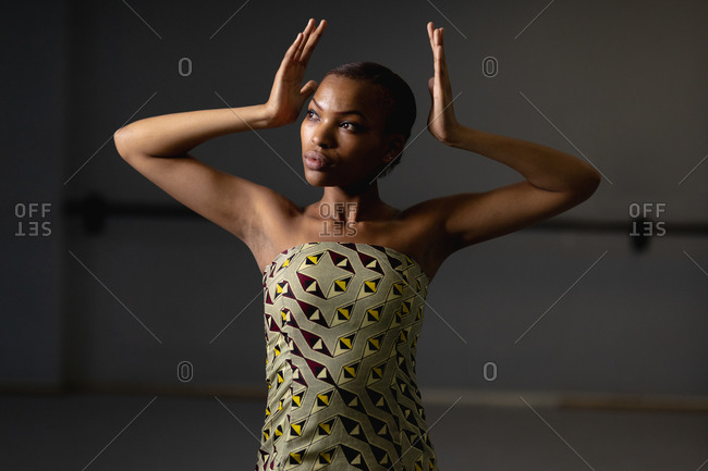 Front view close up of a mixed race female dancer wearing yellow dress, dancing in a studio with her hands up.