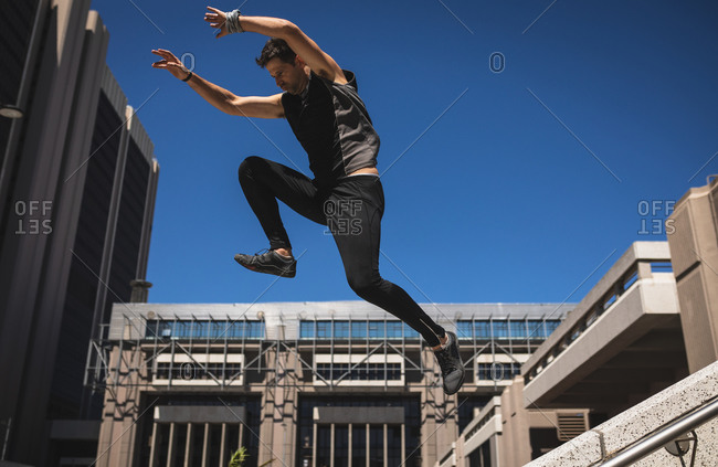 Side view of a Caucasian man practicing parkour by the building in a city on a sunny day, jumping on concrete handrail.