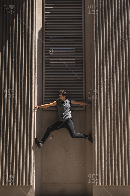 Side view of a Caucasian man practicing parkour by the building in a city on a sunny day, climbing concrete wall of a modern building.