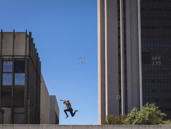 Side view of a Caucasian man practicing parkour by the building in a city on a sunny day, jumping up between modern buildings.