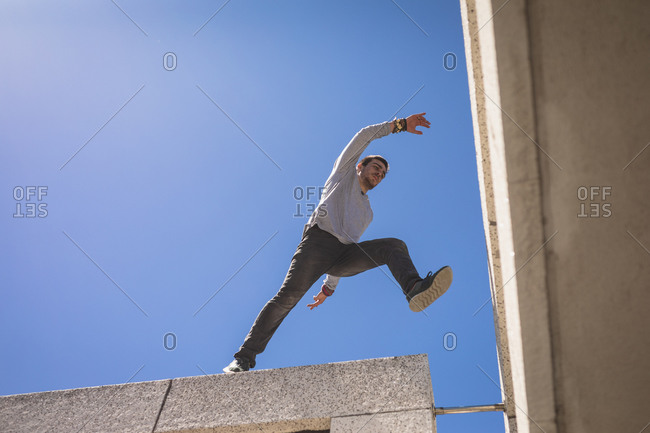 Front low angle view of a Caucasian man practicing parkour by the building in a city on a sunny day, jumping on the rooftop.