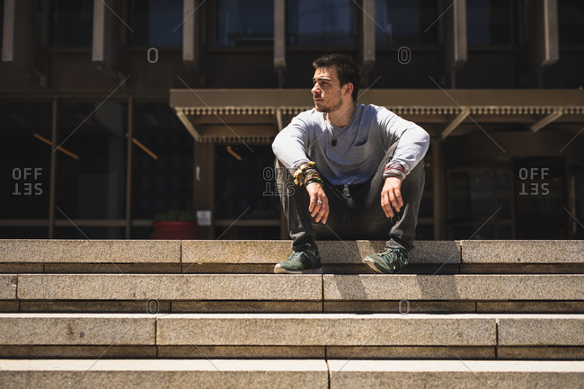 Front view of a Caucasian man practicing parkour by the building in a city on a sunny day, resting taking a break, sitting on the stairs.