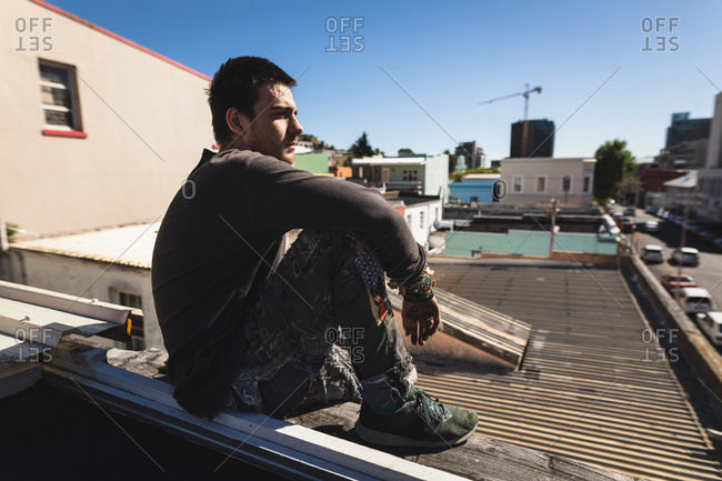 Side view of a Caucasian man practicing parkour by the building in a city on a sunny day, taking a break, resting and sitting on a rooftop.