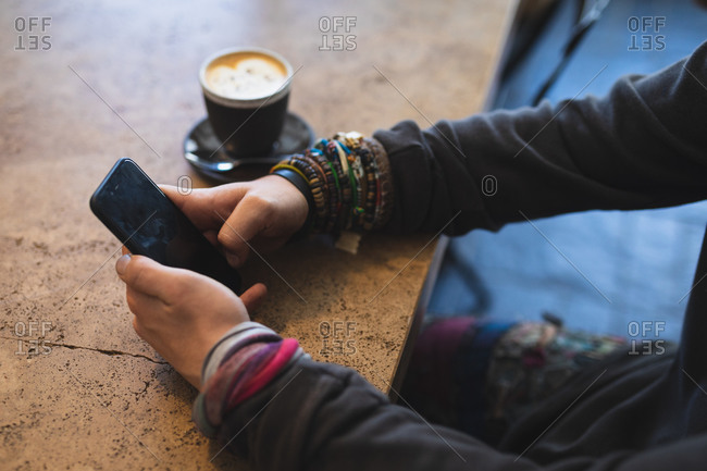 Side view mid section of a Caucasian man wearing casual clothes, sitting by a table in a coffee shop, using his smartphone, with a cup of coffee standing on a table.