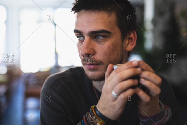 Front view close up of a Caucasian man wearing casual clothes, sitting by a table in a coffee shop, holding a cup of coffee