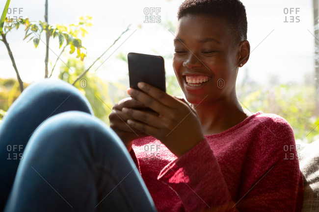 Front view close up of an African American woman sitting in her living room in front of a window on a sunny day, using a smartphone and smiling