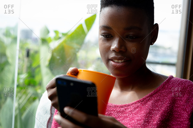 Front view close up of an African American woman sitting in her living room in front of a window on a sunny day, using a smartphone and holding a mug
