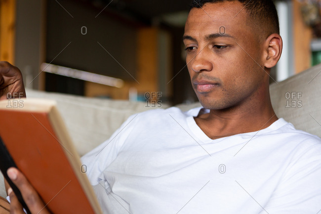 Frond view close up of an African American man hanging out in his living room, sitting on a sofa, reading a book