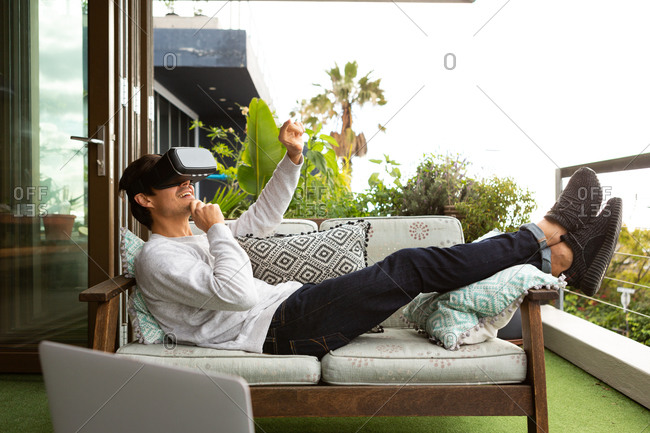 Side view of a Caucasian man hanging out on a balcony on a sunny day, wearing VR goggles, pointing to a virtual screen