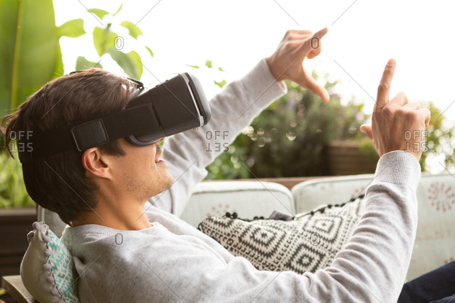 Side view close up of a Caucasian man hanging out on a balcony on a sunny day, wearing VR goggles, pointing to a virtual screen