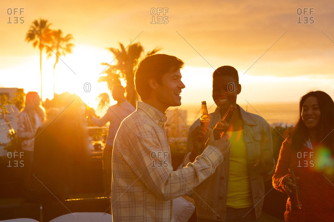 Front view of a multi-ethnic group of friends hanging out on a roof terrace with a sunset sky, holding bottles of beer and smiling