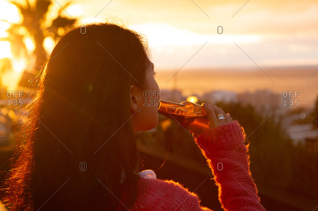 Rear view close up of a mixed race woman hanging out on a roof terrace with a sunset sky, holding a bottle of beer and drinking