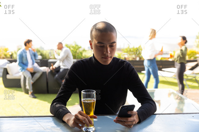 Front view of a mixed race man hanging out on a roof terrace on a sunny day, using a smartphone and holding a glass of beer, with people talking in the background