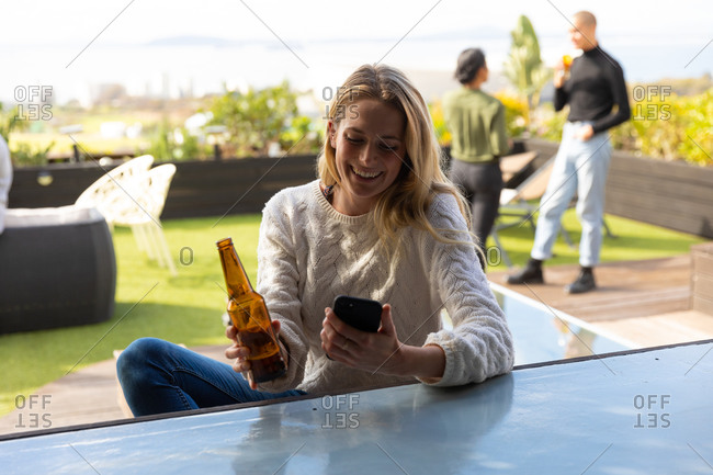 Front view of a Caucasian woman hanging out on a roof terrace on a sunny day, using a smartphone and holding a bottle of beer, smiling, with people talking in the background