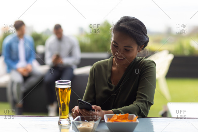Front view of an Asian woman hanging out on a roof terrace on a sunny day, using a smartphone, smiling, a glass of beer beside her on a table, with people talking in the background