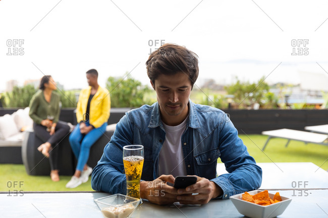 Front view of a Caucasian man hanging out on a roof terrace on a sunny day, using a smartphone, a glass of beer beside him on a table, with people talking in the background