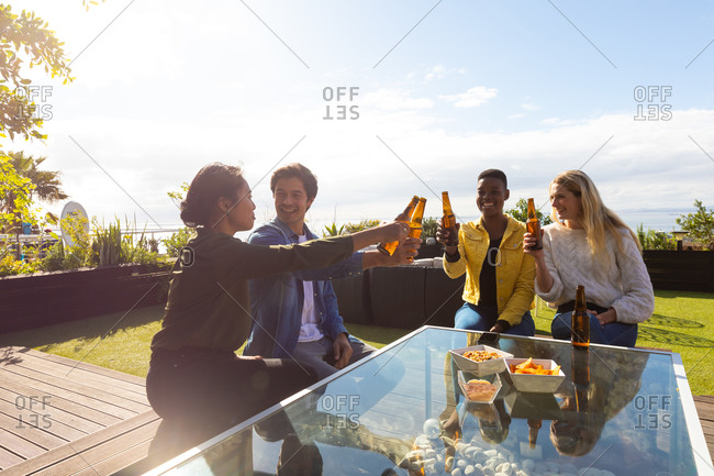 Front view of a multi-ethnic group of friends hanging out on a roof terrace on a sunny day, sitting at a table, holding bottles of beer, making a toast, smiling